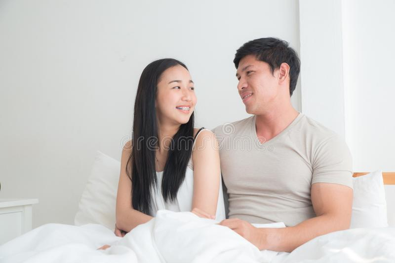 Молодые прекрасные пары на кровати вместе с усмехаться и счастьем стоковое изображение rf