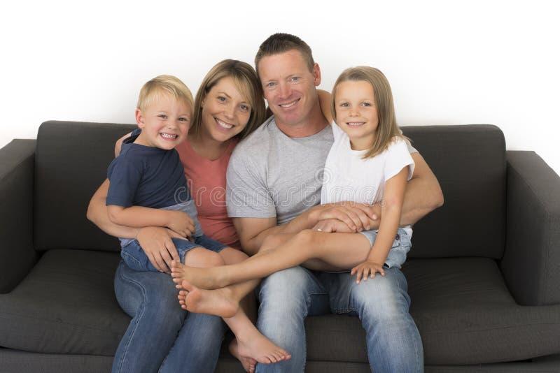 Молодые привлекательные и счастливые пары представляя сидящ дома софа co стоковое фото rf