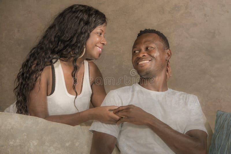 Молодые привлекательные и счастливые черные Афро-американские пары ослабили дома помадку кресла софы говоря наслаждаясь совместно стоковая фотография