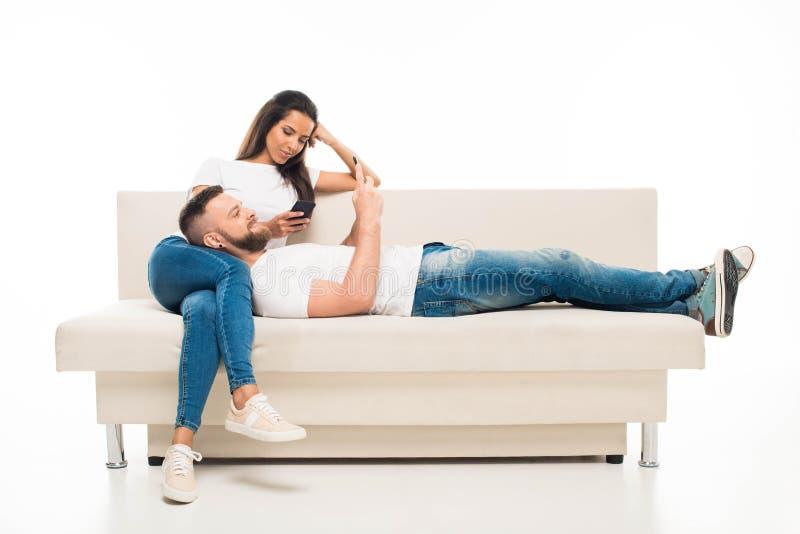 молодые привлекательные пары используя их smartphones на софе, стоковые изображения