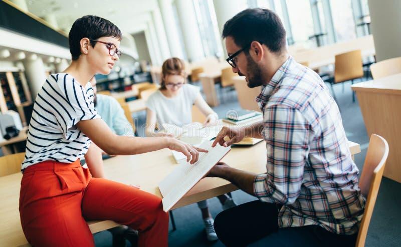 Молодые привлекательные студенты тратя время в библиотеке стоковая фотография rf