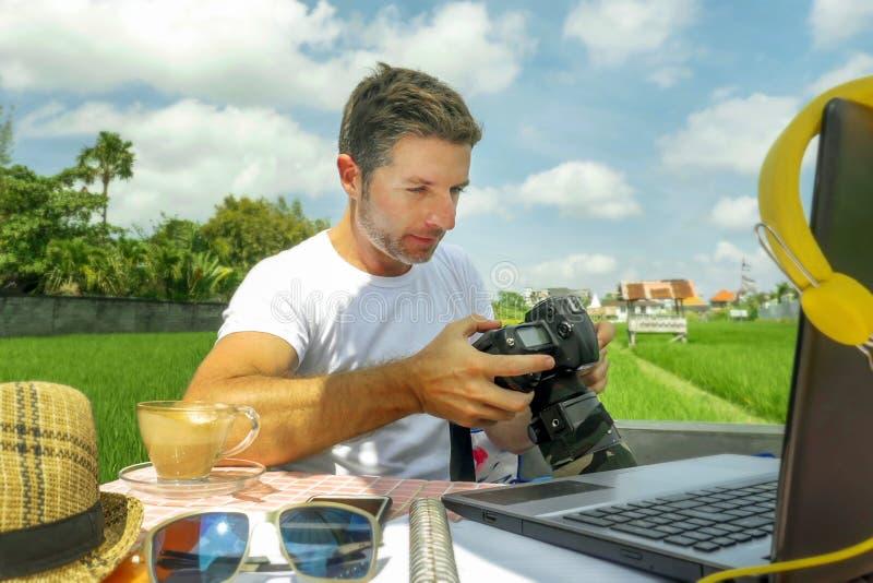 Молодые привлекательные цифровые человек или фотограф кочевника работая на линии outdoors с портативным компьютером и мобильным т стоковая фотография rf