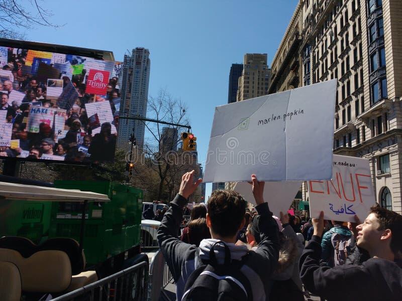 Молодые протестующие около большого внешнего телевидения, марта на наши жизни, против вооруженного насилия, NYC, NY, США стоковое фото rf