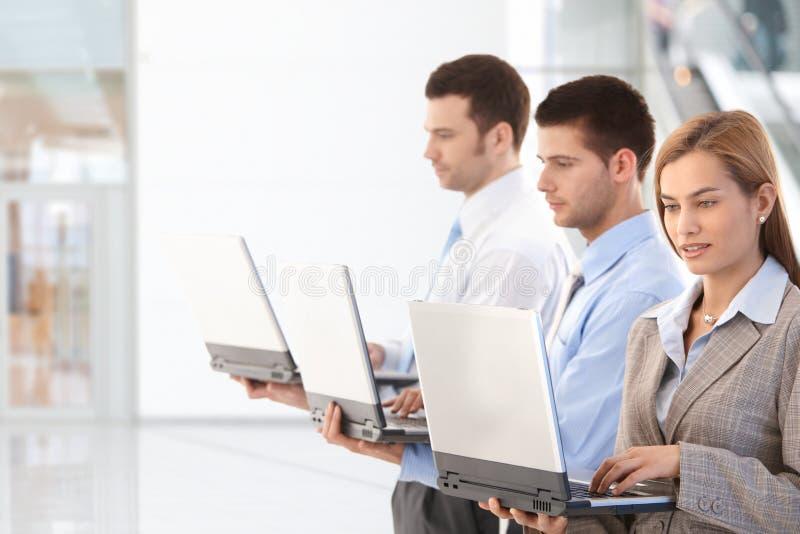 Молодые профессионалы используя компьтер-книжку в лобби офиса стоковые фото