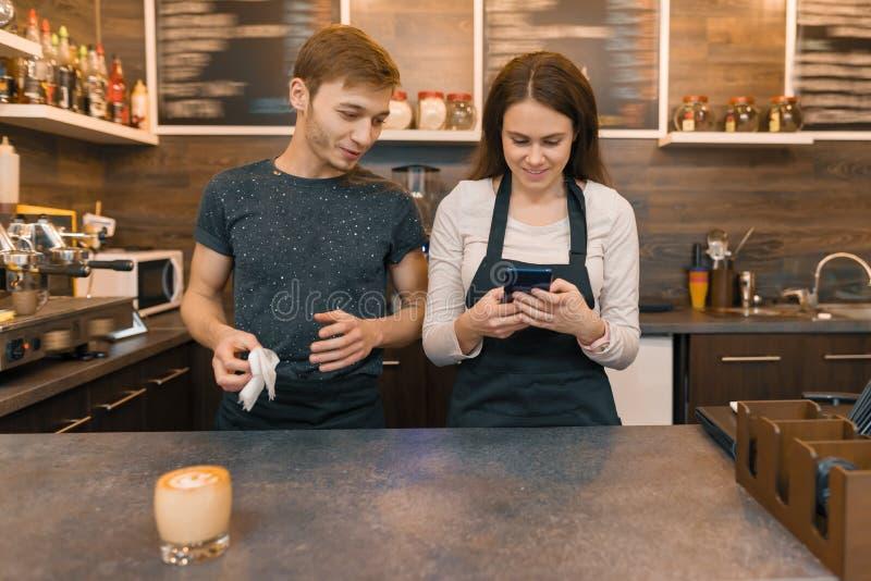 Молодые работники человека кофейни и женщины за счетчиком бара, говоря смотреть в смартфон стоковые изображения