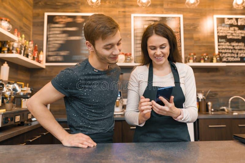 Молодые работники человека кофейни и женщины за счетчиком бара, говоря смотреть в смартфон стоковые фото