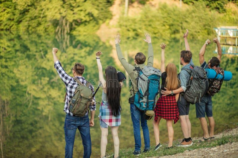 Молодые радостные люди радостны достигнуть верхнюю часть горы стоковые изображения