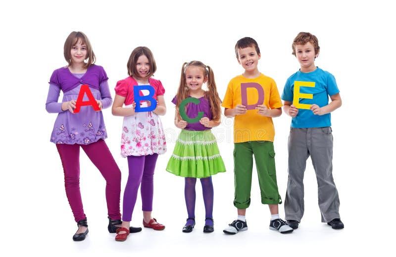 Молодые ребеята школьного возраста держа письма A b c стоковое изображение rf