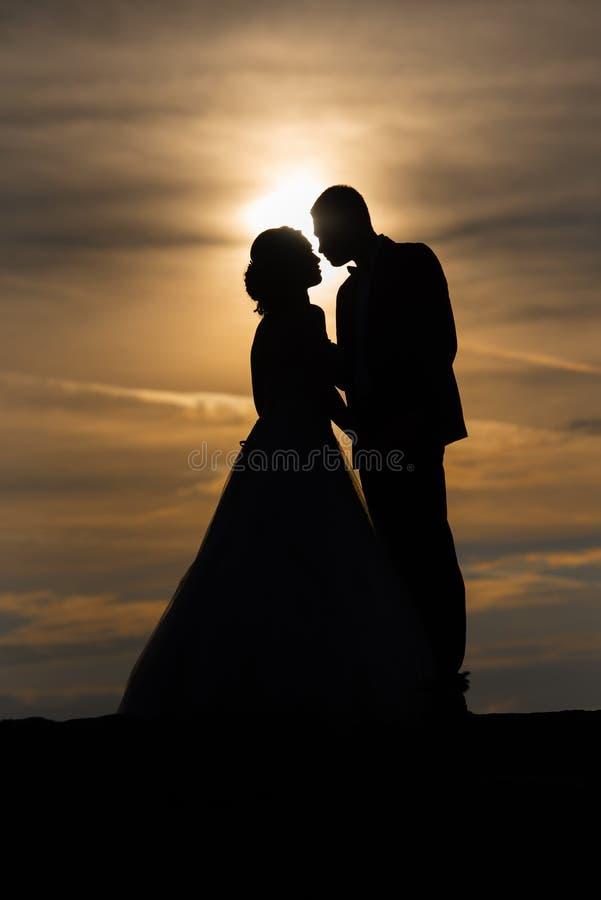 Молодые руки удерживания невесты groom и женщины взрослого мужчины на пляже на заходе солнца стоковое изображение rf