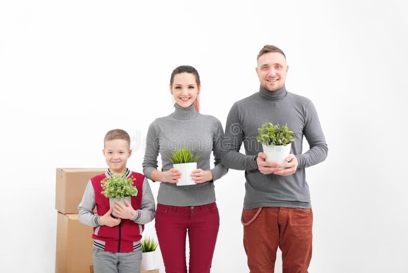 Молодые семья, женщина человека и сын ребенка в новых квартирах Они держат зеленые в горшке заводы Коробки с грузом на a стоковая фотография rf