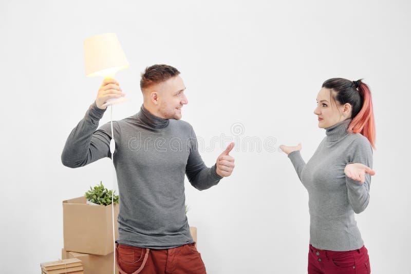 Молодые семья, человек и женщина в новых квартирах Человек имел идею Коробки с грузом на белой предпосылке стоковые фотографии rf