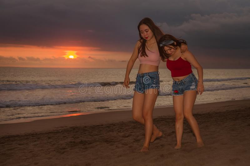 Молодые сестры или азиатская китайская девушка на пляже захода солнца при ее лучший друг имея потеху наслаждаясь летними отпускам стоковые изображения