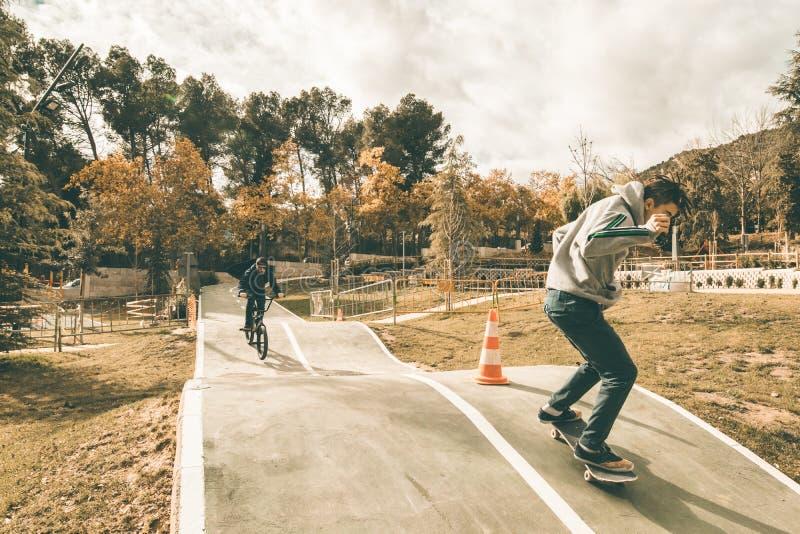 Молодые скейтбордисты и велосипеды bmx Молодые люди практикуя городские спорт стоковые изображения rf