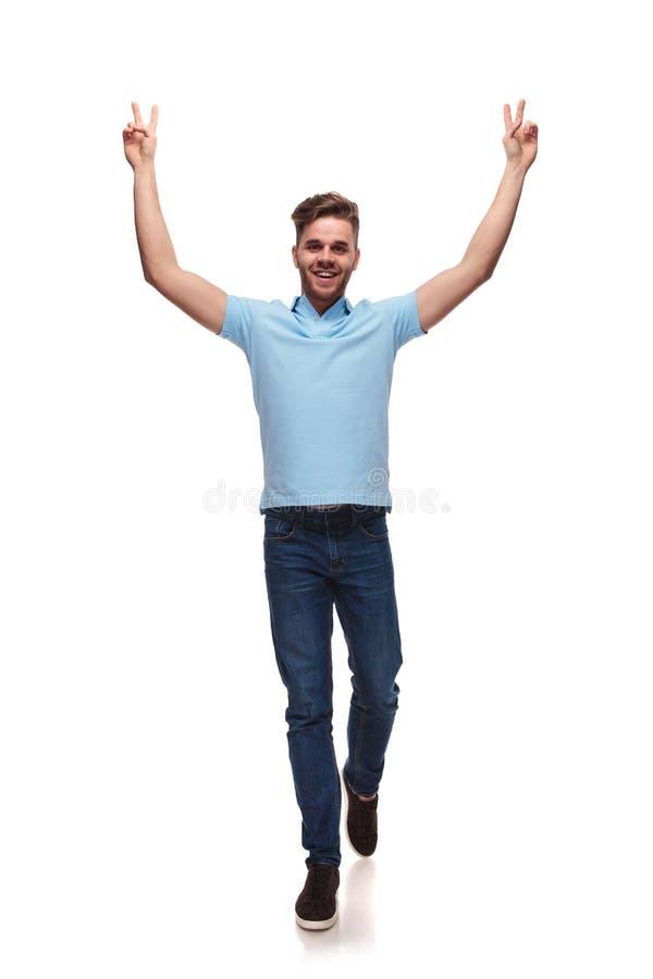 Молодые случайные шаги человека вперед пока празднующ со знаком победы стоковая фотография