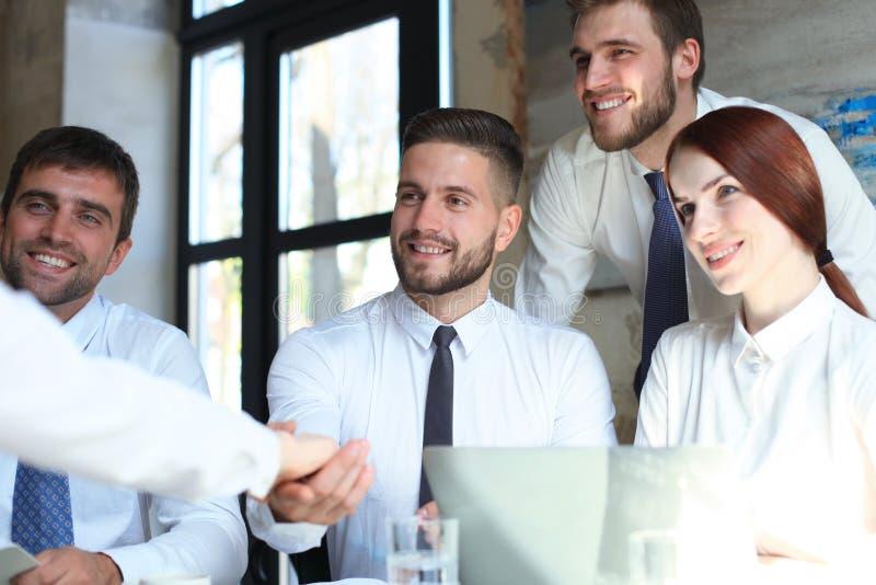Добро пожаловать к нашей команде Молодые современные бизнесмены тряся руки пока работающ в творческом офисе стоковое фото rf