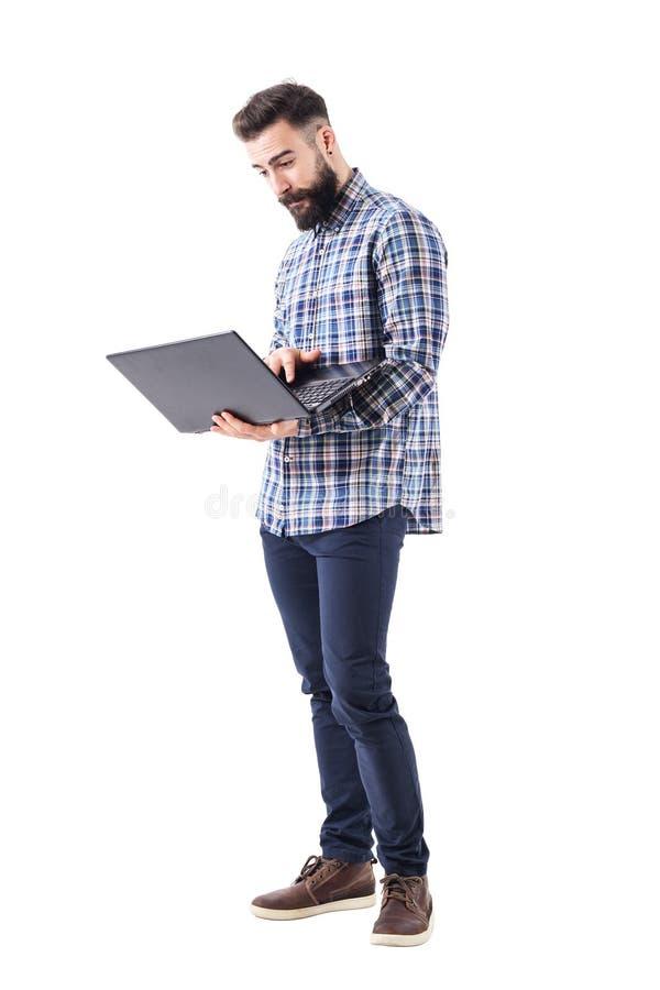 Молодые современные красивые бородатые удерживание работника и портативный компьютер использования стоковая фотография rf
