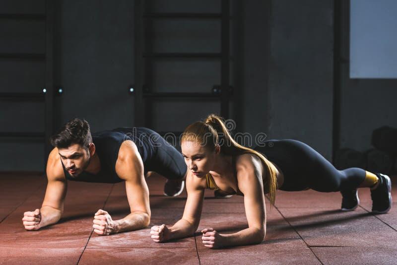 Молодые спортсменка и спортсмен делать нажимает поднимают стоковые фото