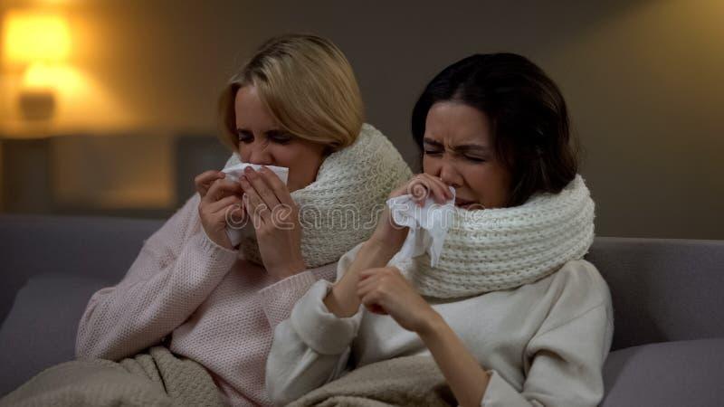 Молодые студенты в шарфах чихая в ткани, гриппе страдания, эпидемии зимы стоковые изображения