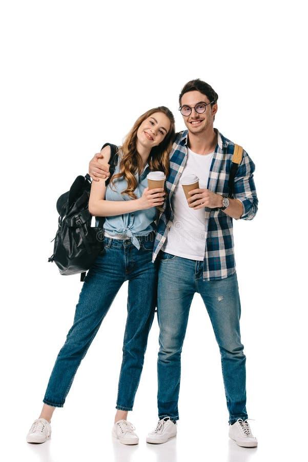 молодые студенты обнимая и держа устранимые кофейные чашки стоковая фотография