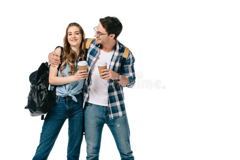 молодые студенты обнимая и держа устранимые кофейные чашки стоковое изображение rf