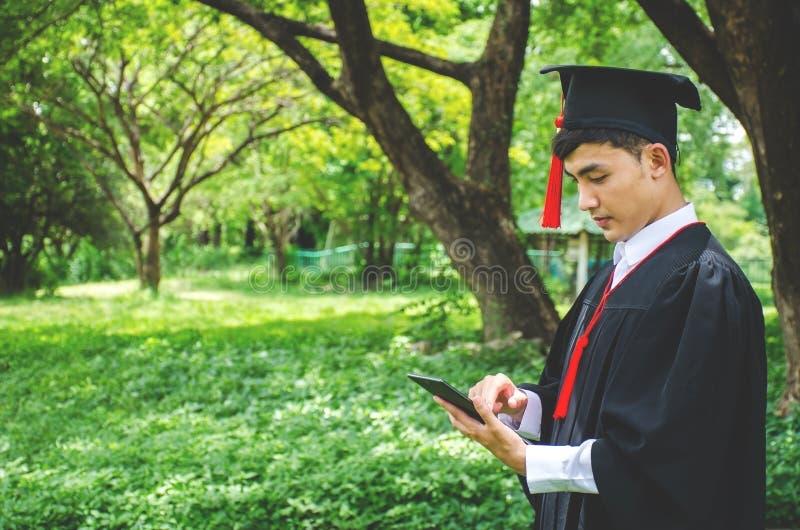 Молодые студенты одетые в черной мантии градации Природа как предпосылка Усмехаться мальчика жизнерадостно, смотря мобильный теле стоковые изображения rf