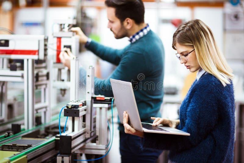 Молодые студенты электроники работая на проекте стоковые изображения