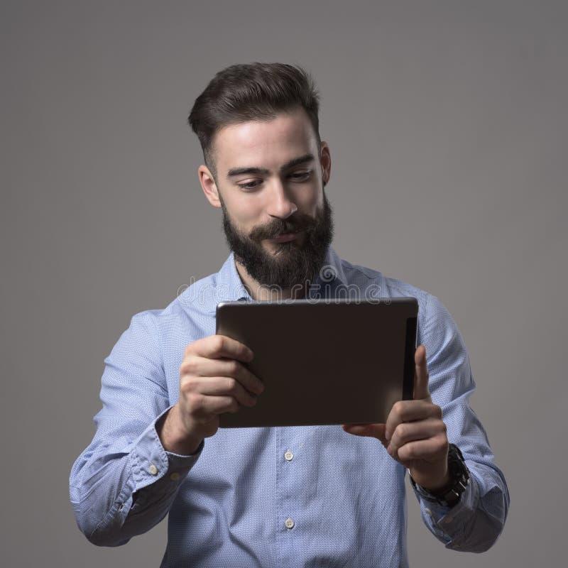 Молодые счастливые бородатые удерживание человека и eBook чтения от планшета сенсорной панели стоковое изображение rf