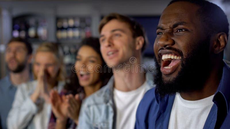 Молодые счастливые вентиляторы празднуя цель, укореняя победу команды, успех чемпионата стоковое изображение