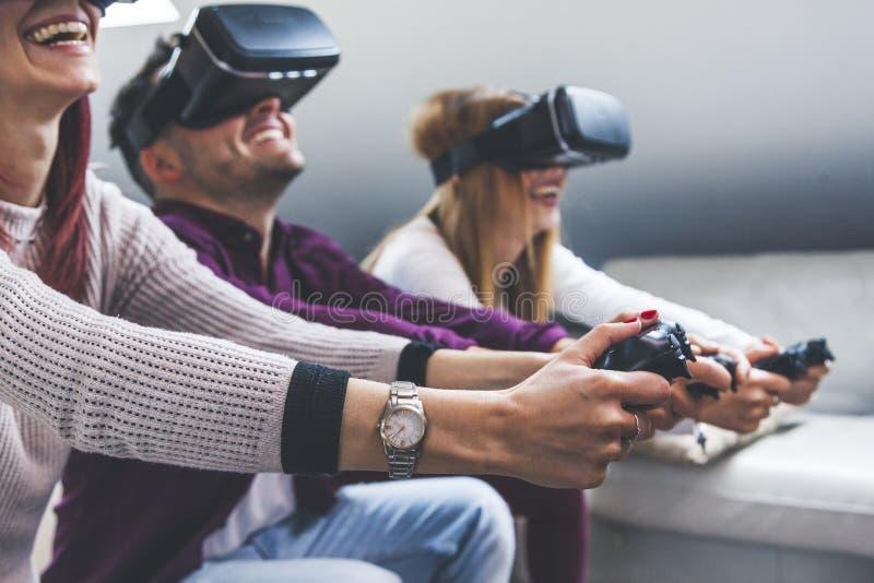 Молодые счастливые 3 друз играя виртуальную реальность видеоигр стоковые фотографии rf