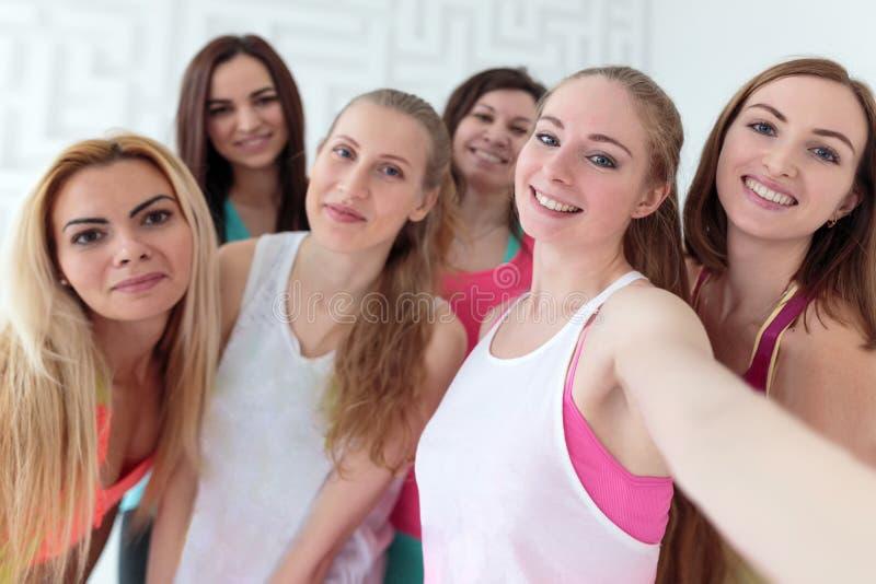 Молодые счастливые женщины одетые в sportswear принимая selfie стоковые фотографии rf