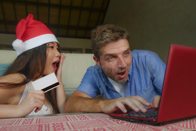 Молодые счастливые и возбужденные смешанные пары этничности с азиатской китайской женщиной в x-m шляпы рождества и кавказского су стоковые фотографии rf