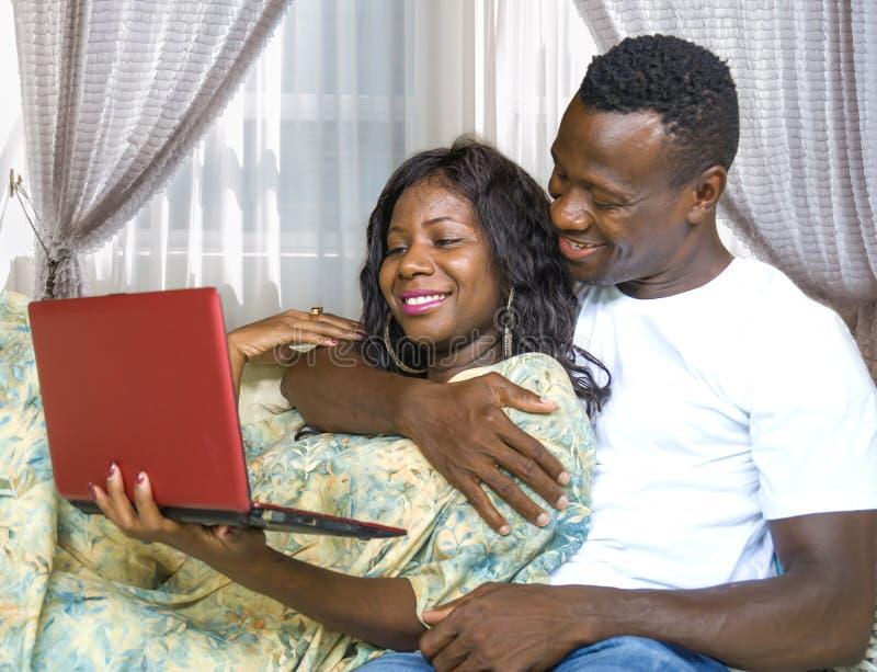 Молодые счастливые и красивые черные афро американские пары в любов наслаждаясь на кресле софы живущей комнаты с сетью ноутбука стоковое фото