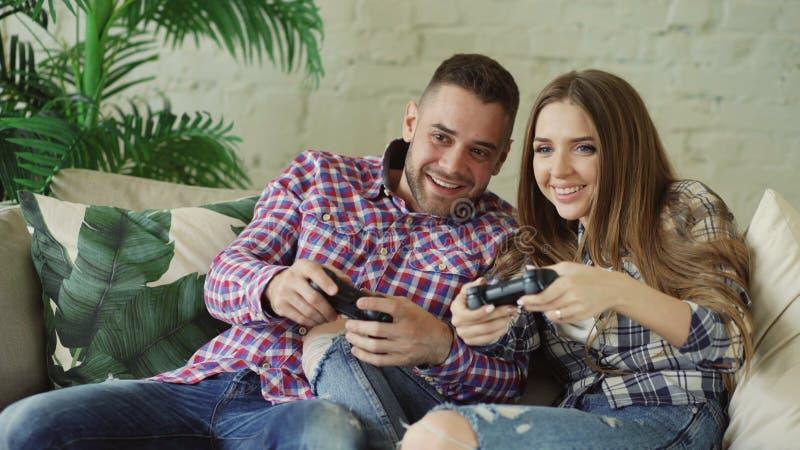 Молодые счастливые и любящие пары играют игру консоли с gamepad и имеют потеху сидя на кресле в живущей комнате дома стоковая фотография rf