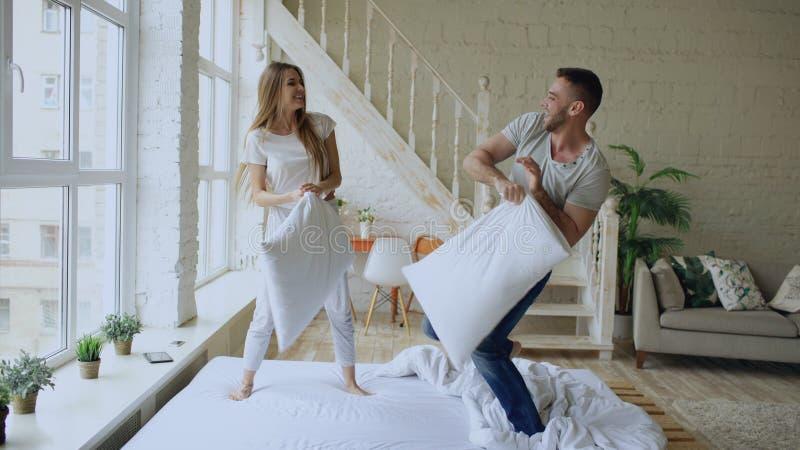 Молодые счастливые и любящие пары имея бой подушками в кровати дома стоковая фотография