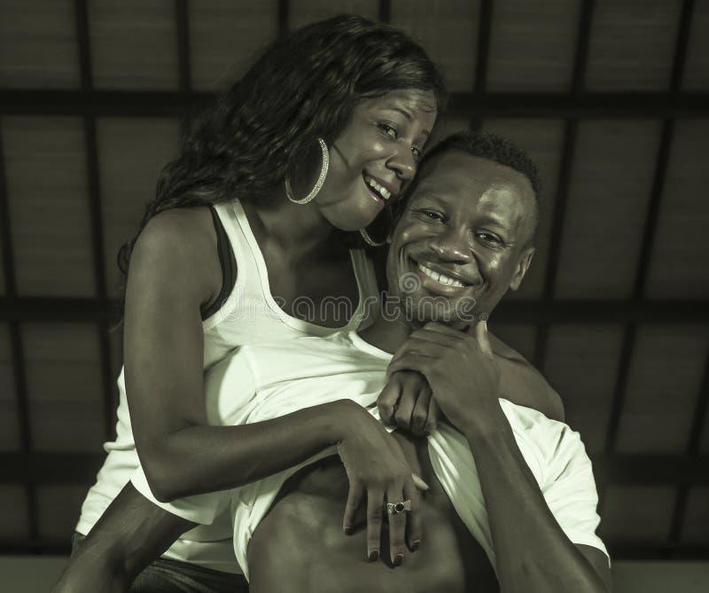 Молодые счастливые и привлекательные черные афро американские пары показ человека 6 брюшков пакета и гордое женщины шаловливого и стоковое фото rf