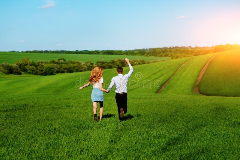 Молодые счастливые любовники бежать на луге с зеленой травой и голубым s стоковые фото