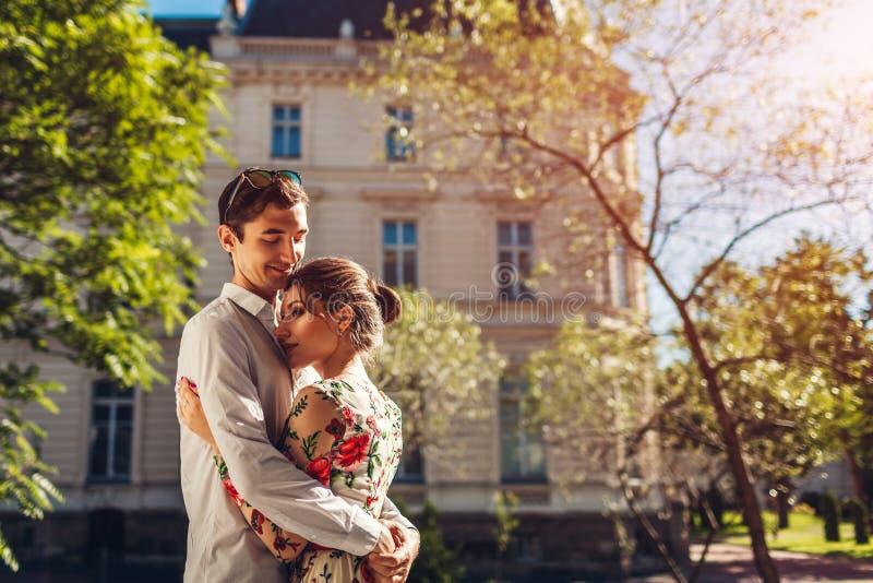 Молодые счастливые пары в влюбленности обнимая outdoors Романтичный человек и женщина идя на улицу города стоковое фото