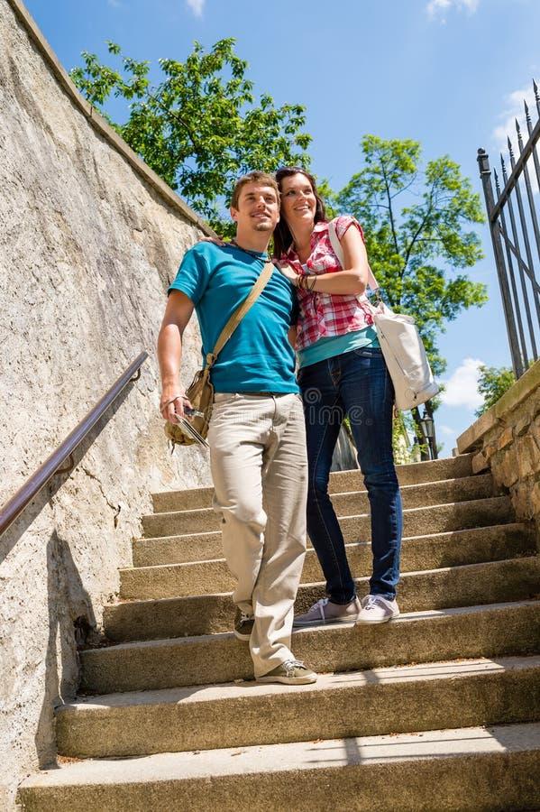 Молодые счастливые пары гуляя вниз с усмехаться лестниц стоковая фотография