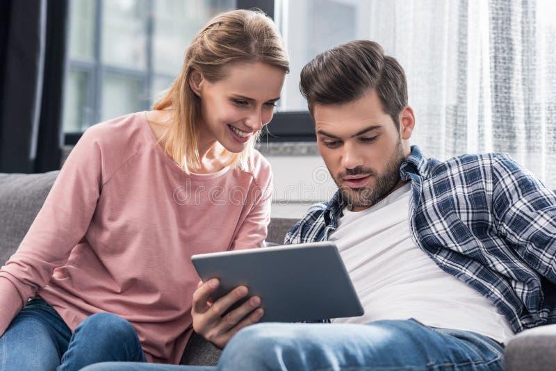 молодые счастливые пары используя цифровую таблетку стоковые изображения
