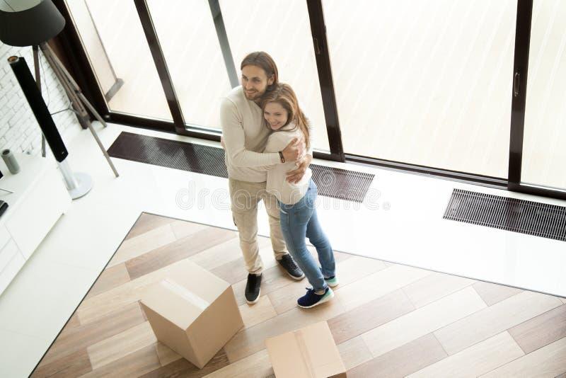 Молодые счастливые пары обнимая в новом доме на moving день стоковое фото