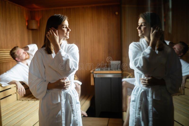 Молодые счастливые пары ослабляя внутри сауны на роскоши гостиницы спа-курорта стоковые фотографии rf