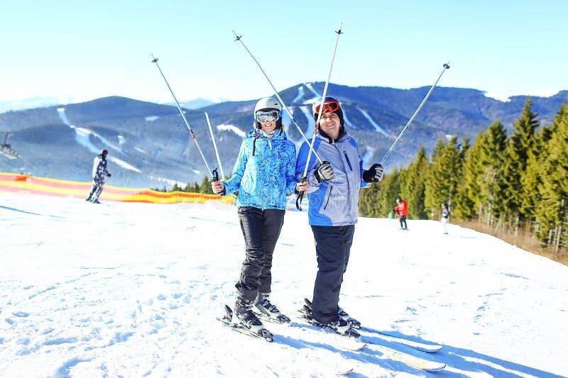 Молодые счастливые пары смотря в снежных горах держа лыжу Селективный фокус стоковые фото