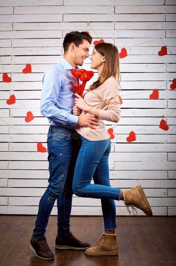 Молодые счастливые пары с сердцем в onbackground рук стоковая фотография