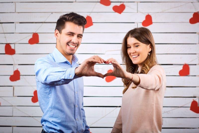 Молодые счастливые пары с сердцем в onbackground рук стоковое фото rf