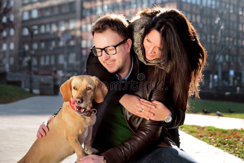 Молодые счастливые пары с собакой наслаждаются в красивом дне стоковое изображение