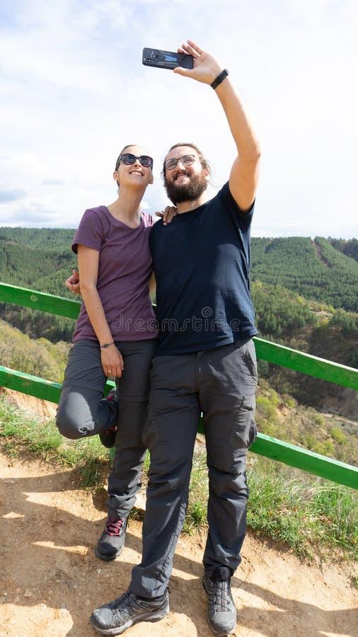 Молодые счастливые пары hiker принимая selfie в горе с умным телефоном стоковое фото rf