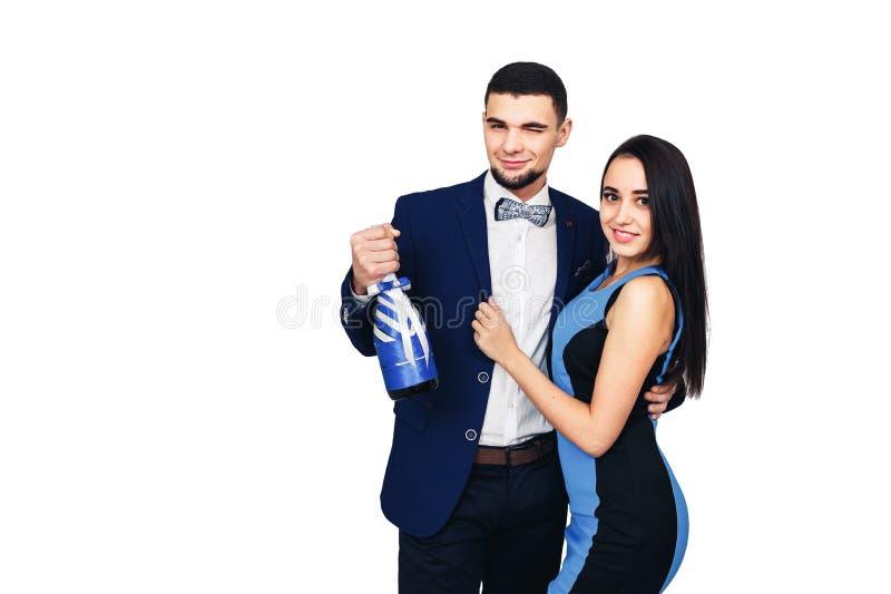 Молодые счастливые стильные пары в голубых одеждах и с украшенной бутылкой шампанского или вина стоковое изображение rf