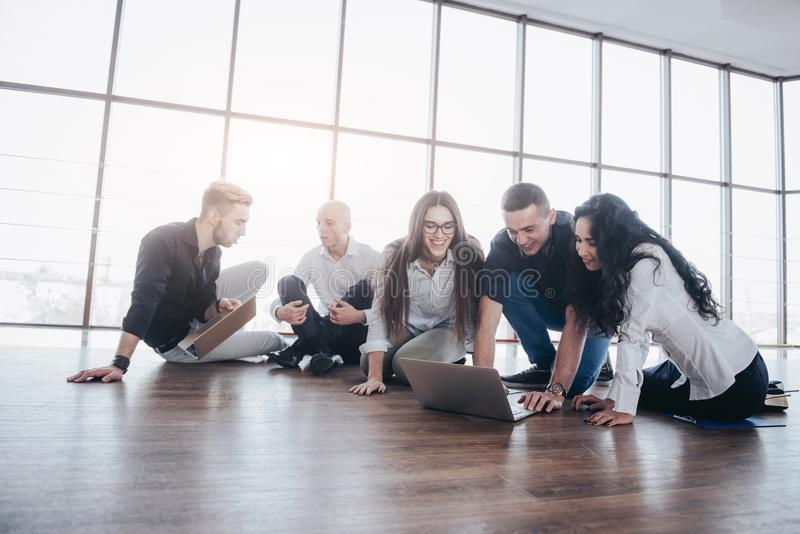 Молодые творческие люди в современном офисе Группа в составе молодые бизнесмены работает вместе с компьтер-книжкой freelancers стоковая фотография rf