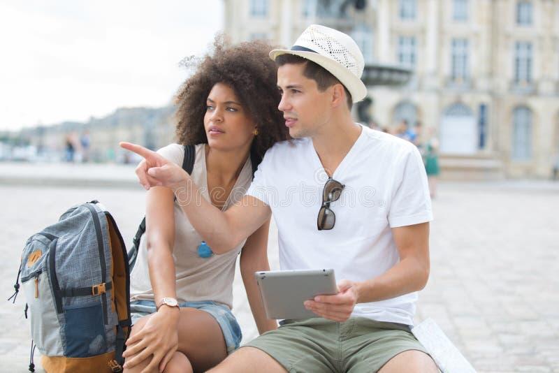 Молодые туристы пар смотря таблетку экранируют outdoors стоковые изображения