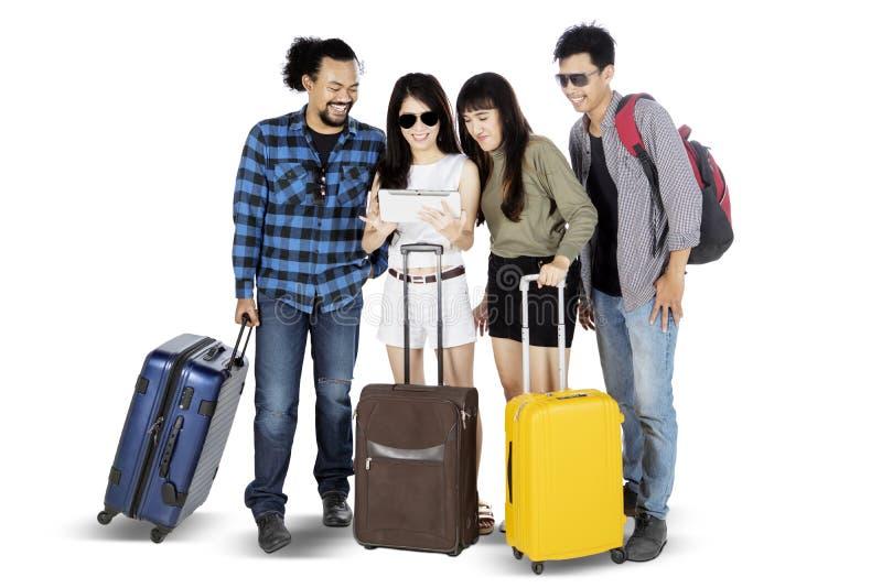 Молодые туристы, смотрящие на цифровой планшет вместе стоковые изображения rf